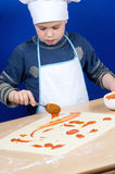 Child putting the pizza ingredients Stock Photo