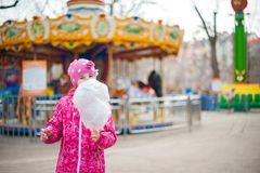 A photograph of a child`s rest on nature in the spring. A child girl in a bright pink jacket is eating sweet cotton wool against t. He backdrop of rides Royalty Free Stock Images