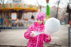 A photograph of a child`s rest on nature in the spring. A child girl in a bright pink jacket is eating sweet cotton wool against t. He backdrop of rides Royalty Free Stock Photography