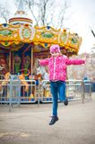 A photograph of a child`s rest on nature in the spring. A child girl in a bright pink jacket is eating sweet cotton wool against t. He backdrop of rides Stock Image