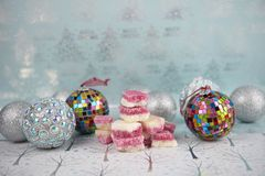 Christmas food photography picture with English old fashioned coconut ice sweets and bauble tree decorations in the background. Photograph of Christmas food Royalty Free Stock Photography