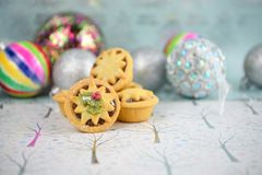 Christmas food photography picture with traditional pastry mince pies and colorful bauble tree decorations in the background stock photography