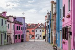 Photograph colourful houses in a square on the island of Burano, Venice. stock photography