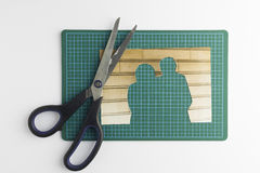 Photograph with cut out people with scissors on green cutting ma. T signifying missing people and broken relationships Royalty Free Stock Photos