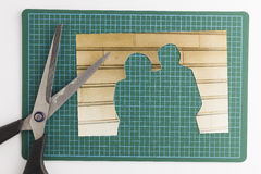 Photograph with cut out people with scissors on green cutting ma. T signifying missing people and broken relationships Stock Image