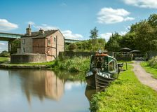 A photograph documenting a converted canal narrowboat acts as a tearoom with a small outdoor garden seating area royalty free stock image