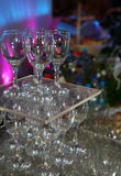 A photograph of an empty transparent colorless glass wine glasses set by the pyramid to decorate the buffet table. On the background of multi-colored mood Royalty Free Stock Photography