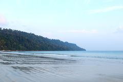 Lush Green Hills, Blue Sky and Picturesque Serene White Sandy Beach - Radhanagar Beach, Havelock Island, Andaman. This is a photograph of the famous Radhanagar stock photo