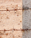 Rusty barb wire tieding on a fence pole Stock Photo