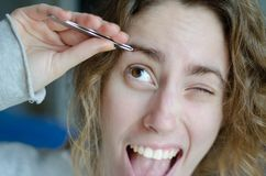 Photograph of a girl plucking her eyebrows with tweezers. royalty free stock image