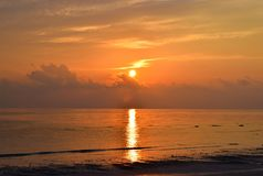 Golden Sun Rising at Horizon with Warm Colors in Sky with Reflection in Sea Water - Kalapathar Beach, Havelock Island, Andaman. This is a photograph of golden royalty free stock image