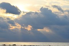Golden Yellow Sunrays Coming from Dark Grey Clouds with Warm Colors in Sky and Still Sea Water - Neil Island, Andaman, India. This is a photograph of golden stock image