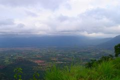 View of Valley and Greenery from Top of Mountain with Clouds in Sky Stock Images