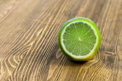 Green lime, close-up. Photograph of half a green lime on a wooden table board. Brown background, focus on bright fruit stock photo