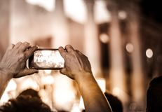 Man recording event with cellphone. Photograph of a man holding a cellphone in his hands recording an event Stock Photography