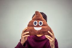 Man with poop emoji cushion. Photograph of a man with poop emoji cushion royalty free stock photos