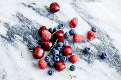 Berries mixture. Photograph of mixture of blueberry, blueberries, raspberry, raspberries, cherry, cherries, stone fruit on a marble slab. This fresh produce Stock Photos