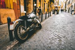 Photograph of Motorcycle Parked Beside Park Bars Near Woman Walking Through Street Royalty Free Stock Photography