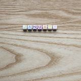 Multicolored January on a wood background. Photograph of Multicolored letter tiles / beads spelling January on a wood background on a square orientation perfect royalty free stock images