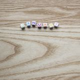 Multicolored January on a wood background. Photograph of Multicolored letter tiles / beads spelling January on a wood background on a square orientation perfect stock image