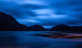 Sunset tones of Caleta Tortel. Photograph of the night landscape of Caleta Tortel, with its tone and lights on the shores of the Pacific ocean. Austral road royalty free stock photography