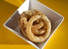Onion Rings. Photograph of onion rings in a square bowl with an orange background royalty free stock photo