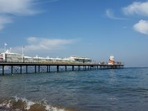 Paignton Pier in Devon, Seaside Resort. Photograph of Paignton pier in Devon UK with its 1980`s pavilion buildings and a carousel at the end. Taken on a sunny stock image