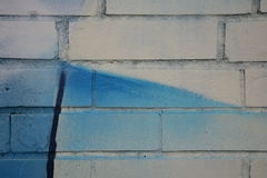 The photograph painted white brick wall with a fragment of graffiti blue with black line Royalty Free Stock Photos