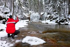 Photograph in red jacket with digital camera in hands is taking photo of winter waterfall Royalty Free Stock Photos