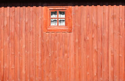 Photograph of a red wooden wall with window. The photograph of a red wooden wall with window Stock Images