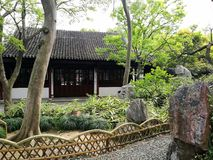 Ancient Chinese garden and house. A photograph showing the beautiful traditional design style china house in a spring garden with green shrubs and trees royalty free stock photography