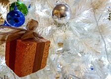 A Photograph showing Decoration of White color Christmas Tree with gift box and blue/silver decorative balls