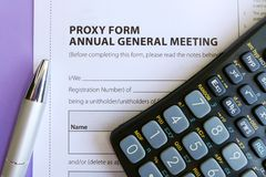 Signing Proxy Form at AGM. A photograph showing an official Proxy form used at a business company AGM - annual general meeting.  Concept image for discussion of Royalty Free Stock Images