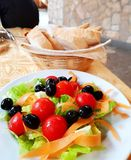 Italian salad with olives. A photograph showing a plate of delicious fresh salad greens with colorful leafy and fruit vegetables such as lettuce, carrots royalty free stock images