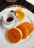 Pancakes for breakfast. A photograph showing a white plate with some pan cakes and a bowl of sweet maple syrup to go along. Decorated with orange slice Stock Image