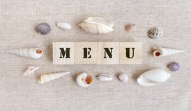 Menu, sea food theme. A photograph showing the word Menu spelt out with stencil printed wooden blocks, surrounded by a ring of assorted sea shells in different Royalty Free Stock Image