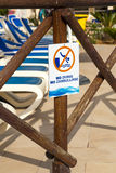 Photograph of sign saying no diving. Sign at the side of a swimming pool saying no diving. Tourist swimming pool in Mallorca, Majorca with sunbeds and sun stock photography