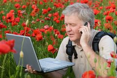 Photograph speaking. Photographer speaking on mobile in poppy field royalty free stock photo