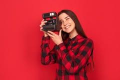 photograph Stellung der jungen Frau lokalisiert auf roten nehmenden Fotos mit dem Lächeln der sofortigen Kamera glücklich stockfoto