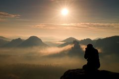 Photograph takes photos of daybreak above  heavy misty valley. Landscape view of misty autumn mountain hills and happy man silhoue Stock Photography