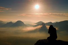 Photograph takes photos of daybreak above  heavy misty valley. Landscape view of misty autumn mountain hills and happy man silhoue Royalty Free Stock Photo