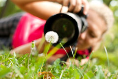 Photograph taking a picture. Female  photograph with camera taking a picture of flower Royalty Free Stock Photography