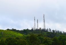 Man versus Nature - Telecommunication and Broadcasting Towers on Top of Green Hills Stock Photo