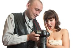 Photograph and topless model working at studio. Two people, photograph and topless model overlooking photoes Royalty Free Stock Image