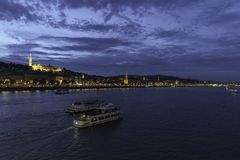 Two ships move away on the Danube as it passes through Budapest with Fishermen`s Bastion and the illuminated Buda shore, Hungary. Photograph of two ships moving stock image