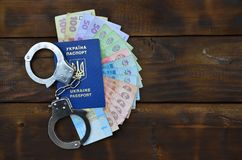 A photograph of a Ukrainian foreign passport, a certain amount of Ukrainian money and police handcuffs. The concept of arresting. Ukrainian illegal immigrants stock image