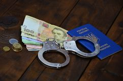 A photograph of a Ukrainian foreign passport, a certain amount of Ukrainian money and police handcuffs. The concept of arresting. Ukrainian illegal immigrants stock photography