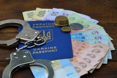 A photograph of a Ukrainian foreign passport, a certain amount of Ukrainian money and police handcuffs. The concept of arresting. Ukrainian illegal immigrants stock photos
