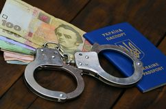 A photograph of a Ukrainian foreign passport, a certain amount of Ukrainian money and police handcuffs. The concept of arresting. Ukrainian illegal immigrants royalty free stock photos