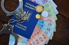 A photograph of a Ukrainian foreign passport, a certain amount of Ukrainian money and police handcuffs. Concept of illegal earnin. Gs of Ukrainian citizens stock image